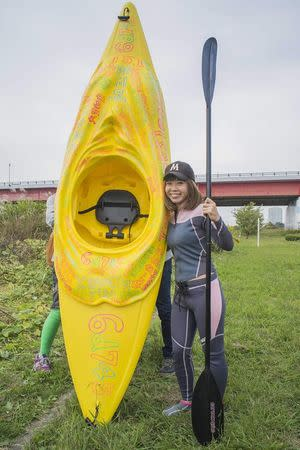 """Japanese artist Megumi Igarashi, known as Rokudenashiko, poses with her kayak modeled on her vagina at the Tama river in Tokyo in this October 19, 2013 picture provided by Eigo Shimojo. Igarashi, who made figures of Lady Gaga and the kayak, said on July 16, 2014 from jail she was """"outraged"""" by her arrest and vowed a court fight against obscenity charges. Igarashi, 42, says she was challenging a culture of """"discrimination"""" against discussion of the vagina in Japanese society. Picture taken October 19, 2013. REUTERS/Eigo Shimojo/Handout via Reuters"""