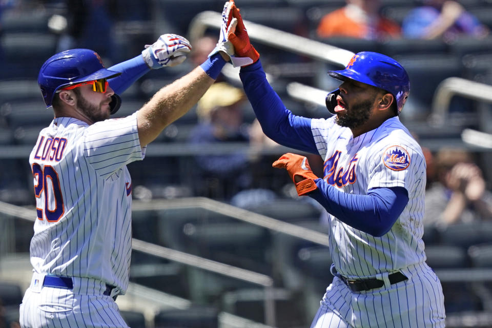 New York Mets' Pete Alonso (20) greets Dominic Smith (2) at the plate after the pair scored on Kevin Pillar's two-run triple during the second inning of a baseball game against the Baltimore Orioles, Wednesday, May 12, 2021, in New York. (AP Photo/Kathy Willens)
