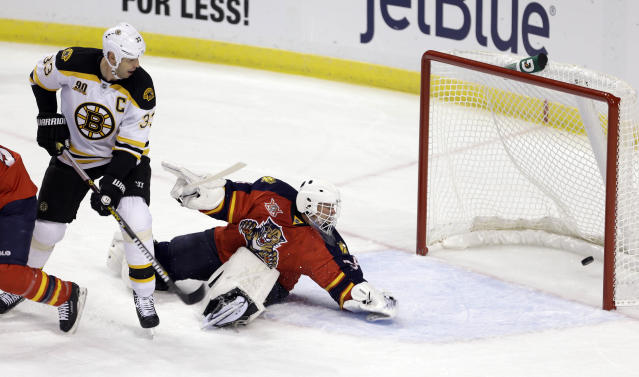 Florida Panthers goalie Tim Thomas (34) is unable to stop a shot by Boston Bruins' Dougie Hamilton as Boston Bruins defenseman Zdeno Chara (33) watches in the first period of an NHL hockey game, Thursday, Oct. 17, 2013, in Sunrise, Fla. (AP Photo/Alan Diaz)
