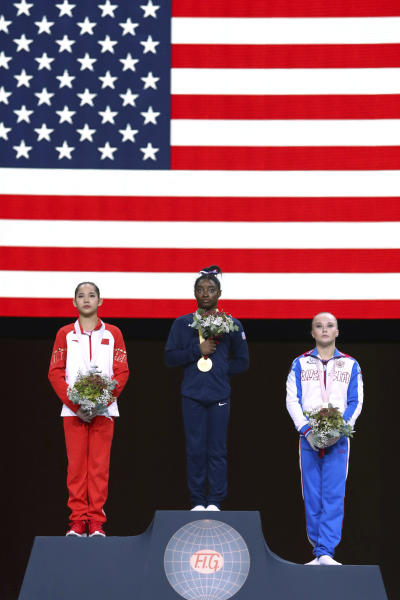 Gold medal winner Simone Biles of the U.S., center, second placed Xijing Tang of China, left, and third placed Angelina Melnikova of Russia celebrate on the podium after the women's all-around final at the Gymnastics World Championships in Stuttgart, Germany, Thursday, Oct. 10, 2019. (AP Photo/Matthias Schrader)
