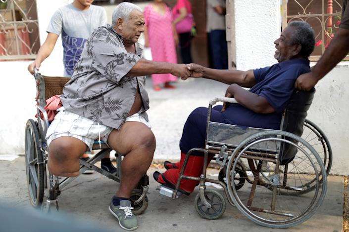 Elimenes Fuenmayor, 65, a patient with kidney disease, greets another kidney disease patient as they wait for the electricity to return during a blackout, in front of a dialysis center in Maracaibo, Venezuela. (Photo: Ueslei Marcelino/Reuters)