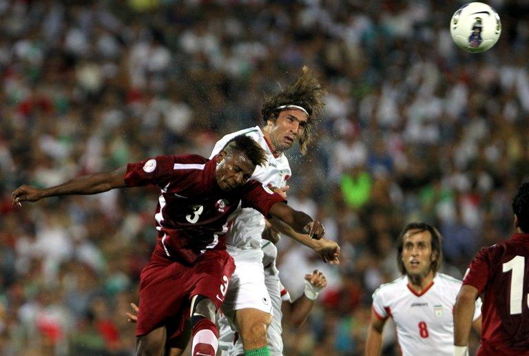 Iran's Hadi Aghily (centre) and Qatar's Mohammad Kasola at the Azadi Stadium in Tehran, Iran on June 12, 2012