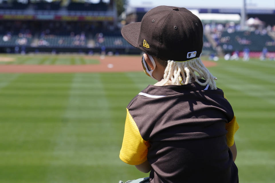 Five-year-old Geronimo Morales wears a hat with fake dreadlocks to mimic San Diego Padres' Fernando Tatis Jr., as he sits on the shoulders of his father, Richard Morales, as they watch the Padres warm up before a spring training baseball game against the Kansas City Royals, Monday, March 22, 2021, in Surprise, Ariz. (AP Photo/Sue Ogrocki)