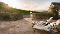 """<p>If you're looking for a beach holiday, Cornwall's north coast is unrivalled – and if you want romance, seclusion and awe-inspiring views, <a href=""""https://boutique-retreats.co.uk/luxury-cottages-cornwall/trebarwith-strand/tremanon-21.html"""" rel=""""nofollow noopener"""" target=""""_blank"""" data-ylk=""""slk:Tremanon"""" class=""""link rapid-noclick-resp"""">Tremanon</a> is hard to beat. Perched on rolling farmland, with the sparkling Atlantic Ocean in front and a wind turbine gently whirling behind, this luxury cliff-top barn conversion offers a sense of freedom that feels truly unique. It may be only a short drive away from the popular village of Tintage, but the only sounds to be heard from the private terrace are the singing of birds and the distant bleating of sheep.</p><p>Inside, Tremanon is welcoming, cosy and impressively eco-friendly, with geothermal underfloor heating and electricity that's generated from its own wind turbine. The living area is light, airy and open-plan; on one end there's a well-equipped kitchen, and on the other, glass doors leading out to the terrace. If you have a thing for sunsets, you're in the right place: the cottage faces west, so in the evenings, you can sit in the armchair and watch the sun sink into the sea right in front of you.</p><p>The A-frame roof is the only sign that this sleek property used to be a barn, and with glass-topped tables, wicker dining chairs and unique design, it all feels wonderfully stylish – though not so much that you feel you can't get comfy on the sofa. A retro cocktail sign adds a dash of fun and the personal touches continue in the two bedrooms and bathrooms, which are packed with organic Cornish toiletries. While Tremanon has room for four, it's ideal for couples seeking quiet seclusion, panoramic views and the space to really unwind.</p>"""