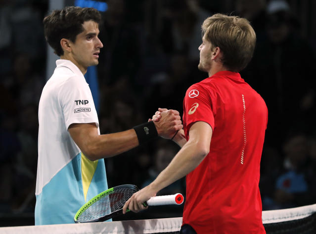 Belgium's David Goffin, right, is congratulated by France's Pierre-Hugues Herbert after winning their second round singles match at the Australian Open tennis championship in Melbourne, Australia, Thursday, Jan. 23, 2020. (AP Photo/Andy Wong)