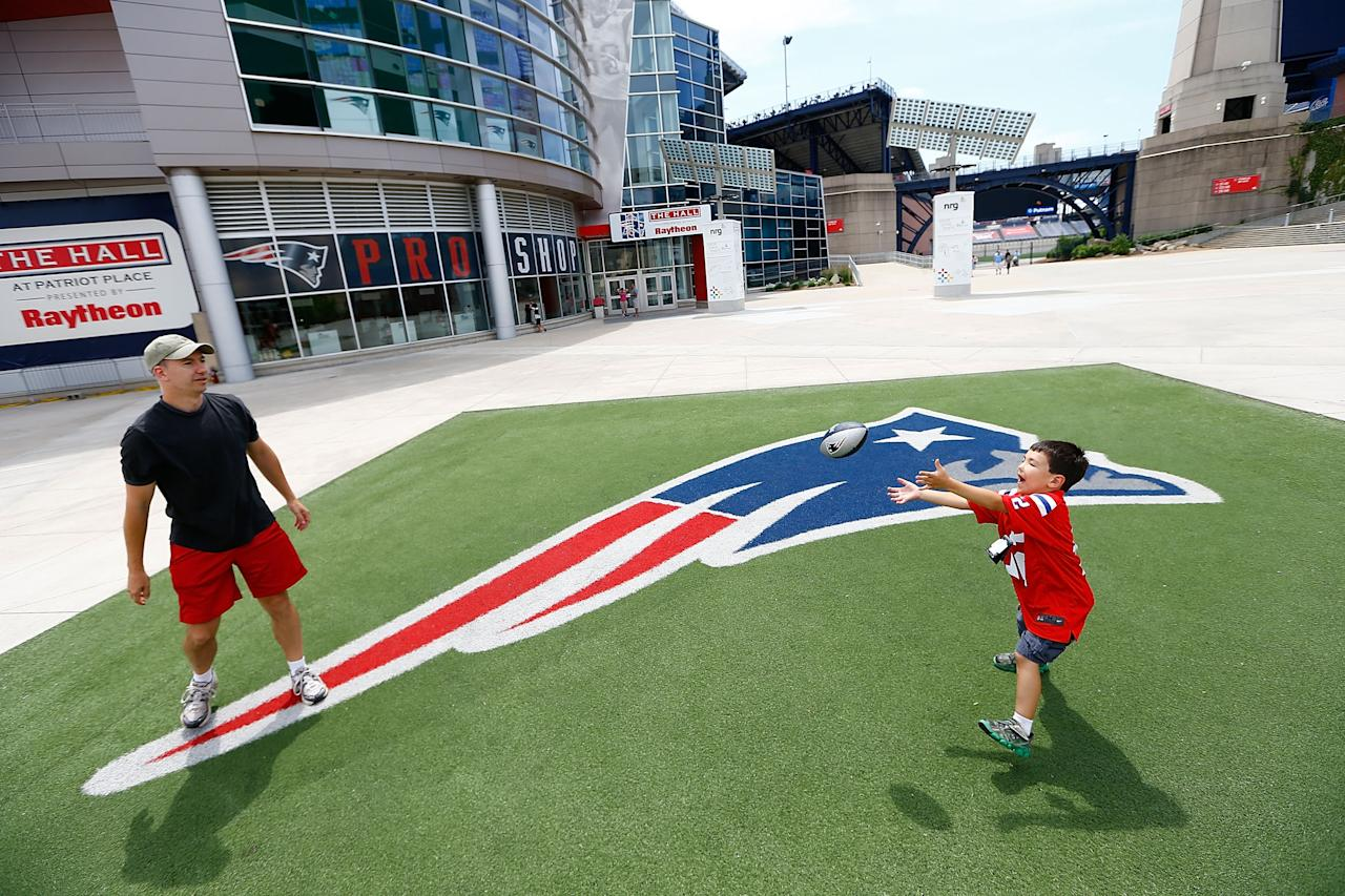 FOXBORO, MA - JULY 7: New England Patriots fans Brian Radzwill (L), and his son Jake (R), play catch after trading in their Aaron Hernandez jersey for a Tom Brady jersey during a free exchange at the pro shop at Gillette Stadium on July 7, 2013 in Foxboro, Massachusetts. (Photo by Jared Wickerham/Getty Images)