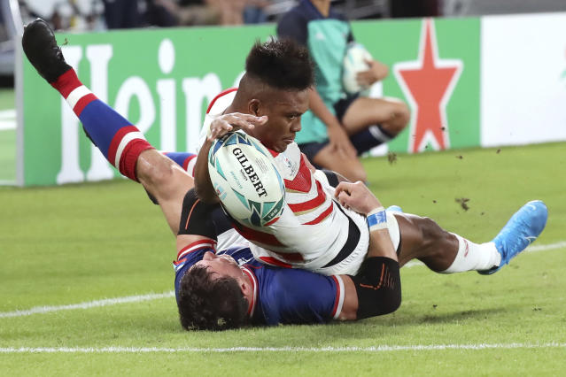 Japan's Kotaro Matsushima, top, makes an attempt to score a try, tackled by Russia's Vasily Artemyev during the Rugby World Cup Pool A game at Tokyo Stadium between Russia and Japan in Tokyo, Japan, Friday, Sept. 20, 2019. The try was disallowed by video referee.(AP Photo/Eugene Hoshiko)