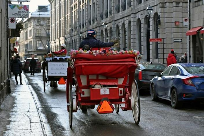 Two horse-drawn carriages pass by in a street of Old Montreal, Quebec, Canada on December 22, 2019.Montreal's horse-drawn carriages will be taken off the roads on December 31, ending a long feud between the city and coachmen and a quaint means of local travel that dates back to the 1600s. (AFP Photo/Eric THOMAS)