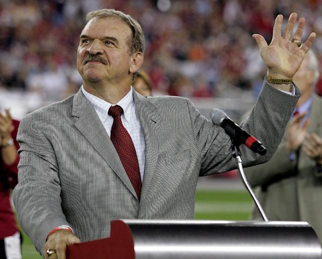 FILE - In this Oct. 16, 2006, file photo,former St. Louis Cardinals offensive lineman Dan Dierdorf waves to fans as he is inducted into the Arizona Cardinals' ring of honor during a ceremony at halftime of a football game against the Chicago Bears in Glendale, Ariz. Hall of Famer Dan Dierdorf is retiring from broadcasting after 43 straight years involved with the NFL. CBS announced Wednesday, Nov. 20, 2013, that he will leave the booth after this season. The 64-year-old Dierdorf has called NFL games for three decades, the longest current tenure by a TV analyst. (AP Photo/Rick Scuteri, File)