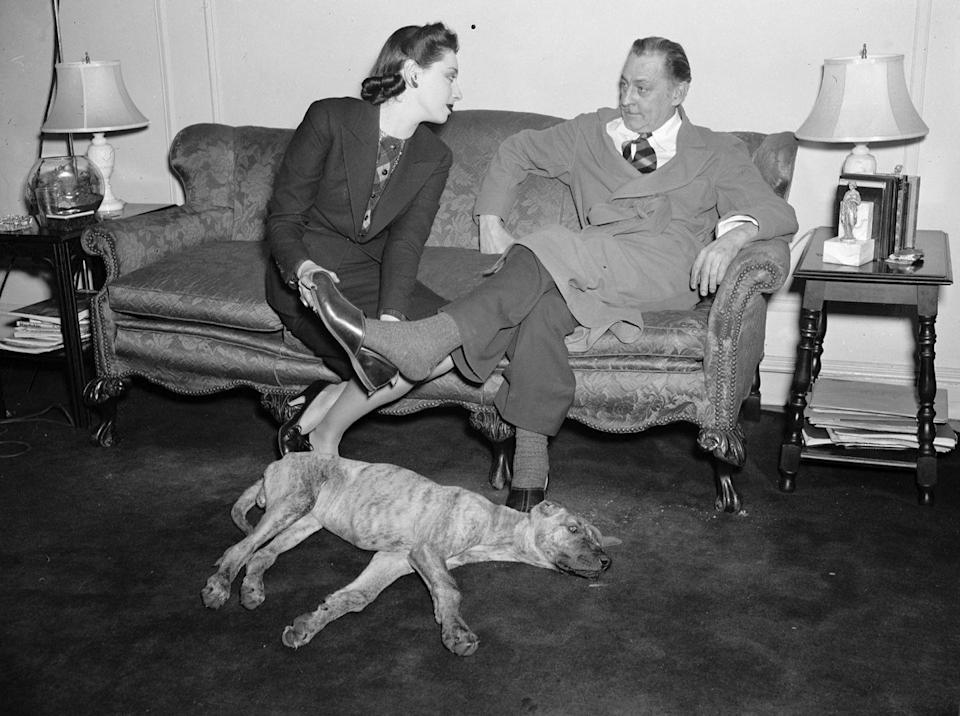 <p>Actress Elaine Barrie puts a slipper on the foot of her husband John Barrymore (grandfather of Drew Barrymore), as they lounge on the sofa with a dog by their side. </p>