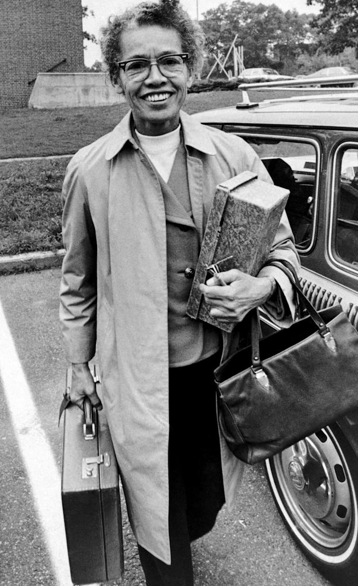 Pauli Murray, in a blazer and overcoat, carries a briefcase.