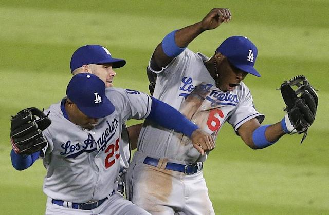 Los Angeles Dodgers left fielder Carl Crawford (25) Los Angeles Dodgers third baseman Jerry Hairston Jr. (6) and Los Angeles Dodgers second baseman Skip Schumaker (55) celebrate after Game 1 of the National League Divisional Series against the Atlanta Braves, Friday, Oct. 4, 2013, in Atlanta. The Dodgers won 6-1. (AP Photo/David Goldman)