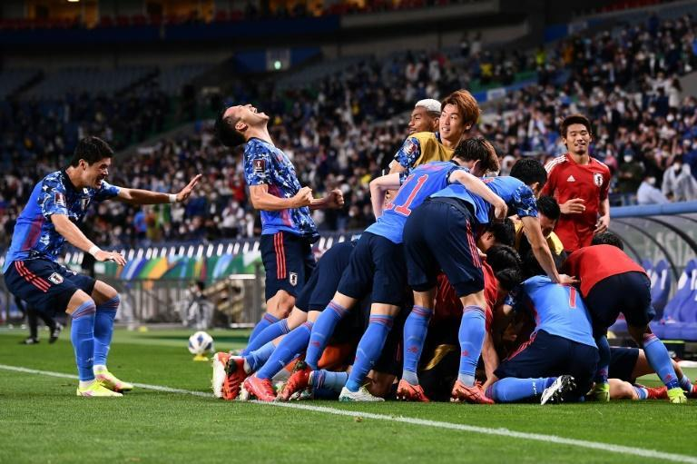 Japan's players celebrated wildly after Australia defender Aziz Behich scored an own goal that handed the Japanese three valuable points (AFP/CHARLY TRIBALLEAU)
