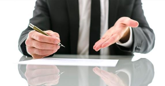 Businessman gesturing to contract | iStock.com