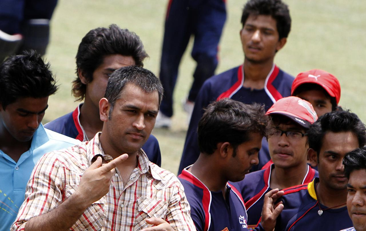 Indian cricket team captain Mahendra Singh Dhoni (R) interacts with the Nepali cricket team at Tribhuvan University Cricket ground in Kathmandu on 16, June 2012. Dhoni arrived in Nepal for a one day visit. AFP PHOTO/ STR        (Photo credit should read STR/AFP/GettyImages)