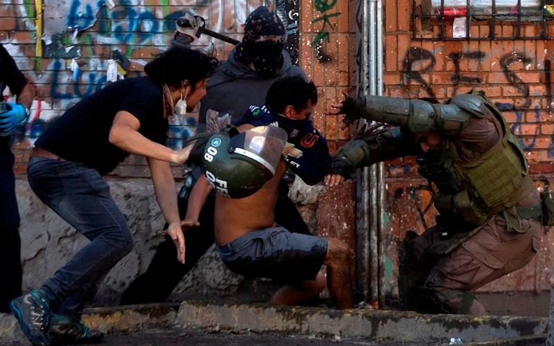 Demonstrators clash with riot police during a protest against the government in Santiago on November 16 - AFP