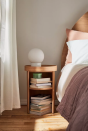 """<p>Use a shelved caddy instead of a bed side table for maximum organisation points, so you can stack things on the top as well as in units below. Useful for books, as shown here, or makeup - whatever you're in need of storage space for, basically!</p><p><a class=""""link rapid-noclick-resp"""" href=""""https://go.redirectingat.com?id=127X1599956&url=https%3A%2F%2Fwww.urbanoutfitters.com%2Fen-gb%2Fshop%2Ftabitha-nightstand%3FinventoryCountry%3DGB%26currency%3DGBP%26color%3D020%26size%3DONE%2BSIZE%26_cclid%3DGoogle_Cj0KCQjw1ouKBhC5ARIsAHXNMI_2Dt7pHFFmStd0-99JkNjhJEW5wf8OqB3N7ElV30p7B4Dupw0L1mAaAvCFEALw_wcB%26gclid%3DCj0KCQjw1ouKBhC5ARIsAHXNMI_2Dt7pHFFmStd0-99JkNjhJEW5wf8OqB3N7ElV30p7B4Dupw0L1mAaAvCFEALw_wcB%26type%3DREGULAR%26quantity%3D1&sref=https%3A%2F%2Fwww.cosmopolitan.com%2Fuk%2Finteriors%2Fg3725%2Fclever-storage-solutions%2F"""" rel=""""nofollow noopener"""" target=""""_blank"""" data-ylk=""""slk:SHOP NOW"""">SHOP NOW</a></p>"""