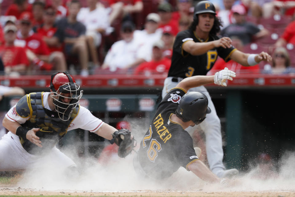 Pittsburgh Pirates' Adam Frazier (26) scores against Cincinnati Reds catcher Tucker Barnhart, left, on a two-run double by Bryan Reynolds off relief pitcher David Hernandez in the eighth inning during the first baseball game of a doubleheader, Monday, May 27, 2019, in Columbus. (AP Photo/John Minchillo)