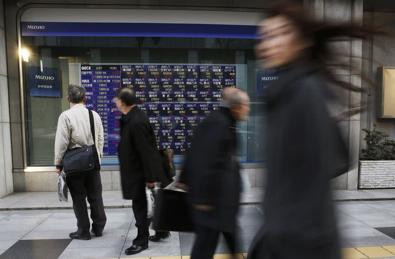 A man (L) looks at a stock quotation board as passers-by walk past, outside a brokerage in Tokyo February 27, 2015. REUTERS/Toru Hanai/Files