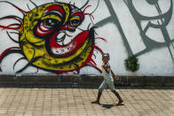 """A child walks past a COVID-19 graffiti in Soweto's Orlando West township near Johannesburg, South Africa, Thursday Nov. 19, 2020. Africa has surpassed 2 million confirmed coronavirus cases as the continent's top public health official warns that """"we are inevitably edging toward a second wave"""" of infections. The 54-nation continent of 1.3 billion people is being warned against """"prevention fatigue"""" as countries loosen pandemic restrictions to ease their economies' suffering and more people travel. (AP Photo/Jerome Delay)"""
