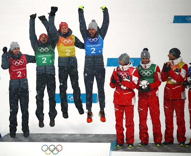 Nordic Combined Events - Pyeongchang 2018 Winter Olympics - Men's Team 4 x 5 km Final - Alpensia Cross-Country Skiing Centre - Pyeongchang, South Korea - February 22, 2018 - Gold medalists Vinzenz Geiger, Fabian Riessle, Eric Frenzel and Johannes Rydzek of Germany celebrate during the victory ceremony as bronze medalists Austria look on. REUTERS/Carlos Barria