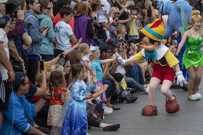Two costumed performers speak to a crowd; one high-fives a little girl.