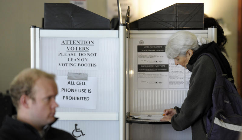 As a District of Columbia resident, left, waits to cast their vote, another votes at right, as early voting continued in Washington, Wednesday, Oct. 31, 2012. (AP Photo/Susan Walsh)