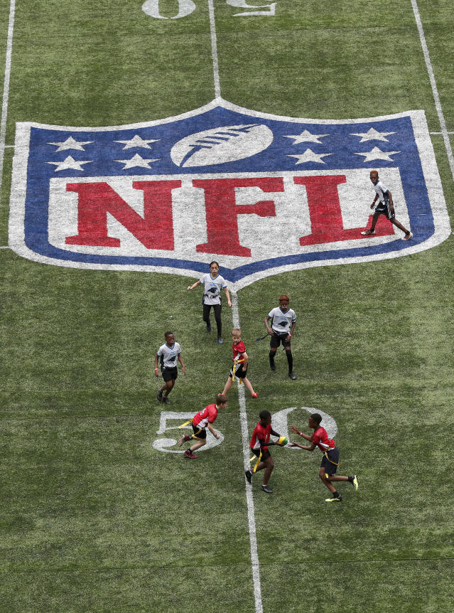 Youngsters play on the pitch during the final tournament for the UK's NFL Flag Championship, featuring qualifying teams from around the country, at Tottenham Hotspur Stadium in London, Wednesday, July 3, 2019. The new stadium will host its first two NFL London Games later this year when the Chicago Bears face the Oakland Raiders and the Carolina Panthers take on the Tampa Bay Buccaneers. (AP Photo/Frank Augstein)