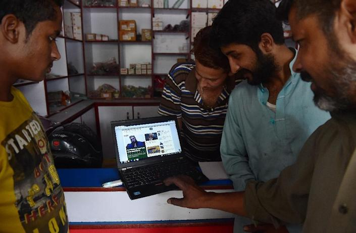 Pakistanis browse the Khabaristan Times website at a store in Rawalpindi (AFP Photo/Farooq Naeem)