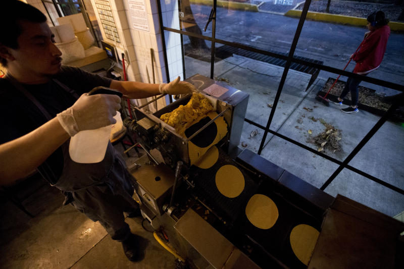 Chef Jesus Saldivar feeds ground corn through the tortilla making machine at El Pujol Mill in the Condesa neighborhood of Mexico City, Tuesday, April 9, 2019. The shop is part of a new tortilla movement launched by a handful of chefs, restaurants and organizations to restore and popularize authentic tortillas, made of only corn, water and lime or calcium carbonate. (AP Photo/Rebecca Blackwell)