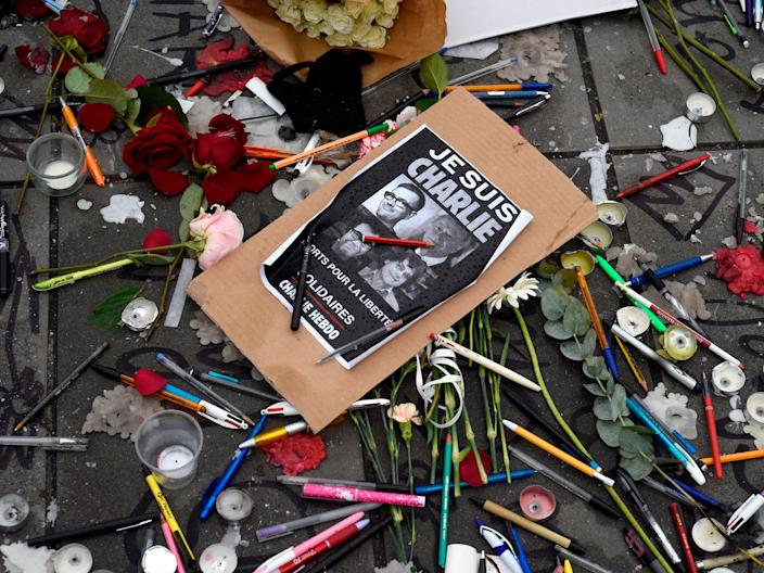 "Pens and pencils are placed on the ground near a sign with the portraits of late Charlie Hebdo editor Stephane Charbonnier (aka Charb), late French cartoonists Georges Wolinski, Bernard Verlhac (aka Tignous) and Jean Cabut (aka Cabu) on the Place de la Republique (Republic Square) in Paris on January 8, 2015, following an attack on the offices of the French satirical newspaper Charlie Hebdo in Paris on January 7 by armed gunmen which left 12 dead. <p class=""copyright""><a href=""https://www.gettyimages.com/detail/news-photo/pens-and-pencils-are-placed-on-the-ground-near-a-sign-with-news-photo/461164740?adppopup=true"" rel=""nofollow noopener"" target=""_blank"" data-ylk=""slk:MARTIN BUREAU/AFP via Getty Images"" class=""link rapid-noclick-resp"">MARTIN BUREAU/AFP via Getty Images</a></p>"