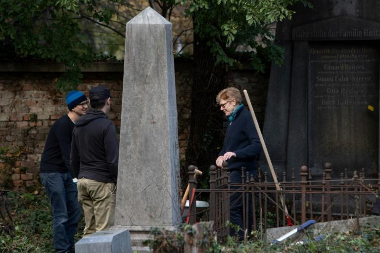 Volunteers including Greens councillor Jennifer Kickert (R) work in the Waehring cemetery
