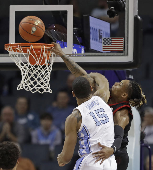 Louisville's Khwan Fore, back, is fouled by North Carolina's Garrison Brooks (15) during the first half of an NCAA college basketball game in the Atlantic Coast Conference tournament in Charlotte, N.C., Thursday, March 14, 2019. (AP Photo/Chuck Burton)