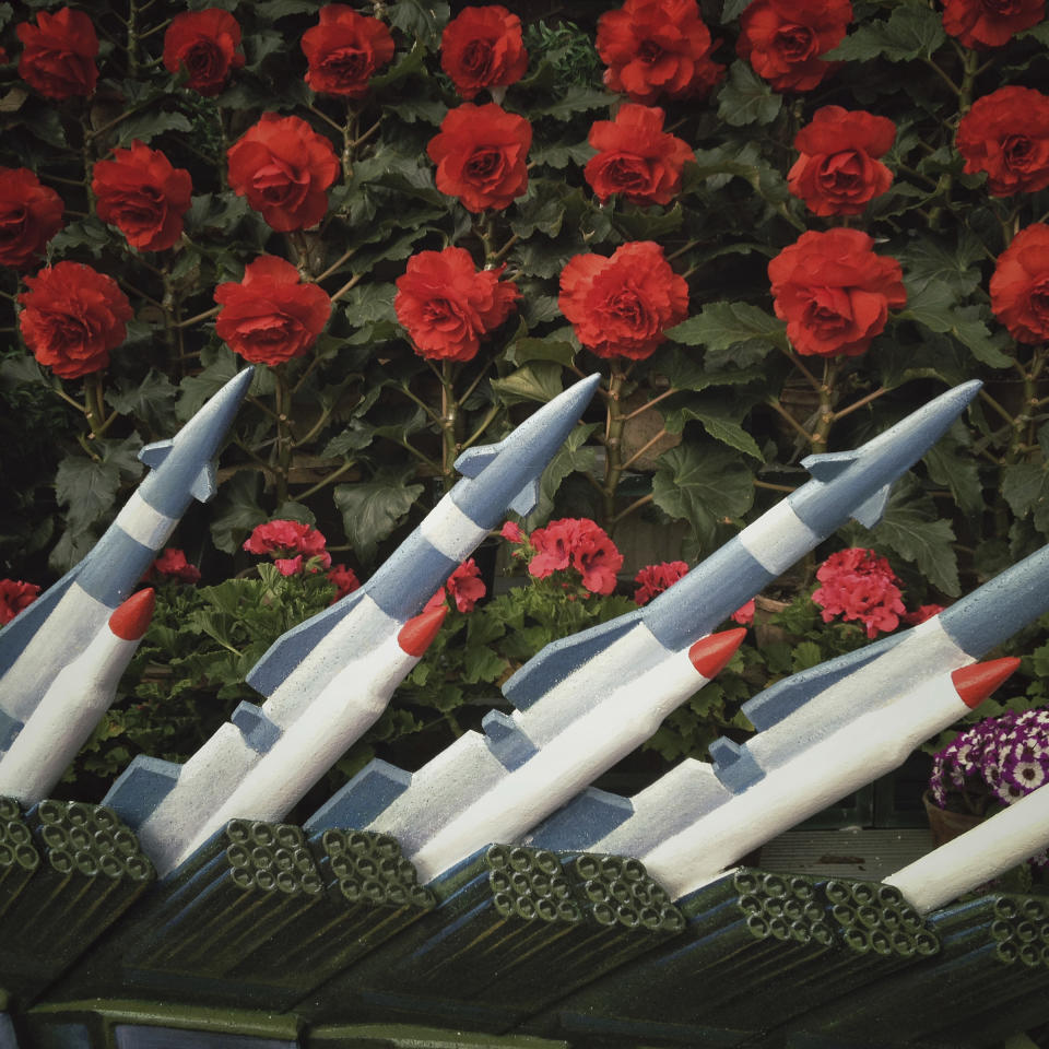 "In this April 12, 2013 photo, models of North Korean rockets are placed next to ""Kimjongilia"" flowers, named after the late leader Kim Jong Il, at a flower show in Pyongyang, North Korea. (AP Photo/David Guttenfelder)"