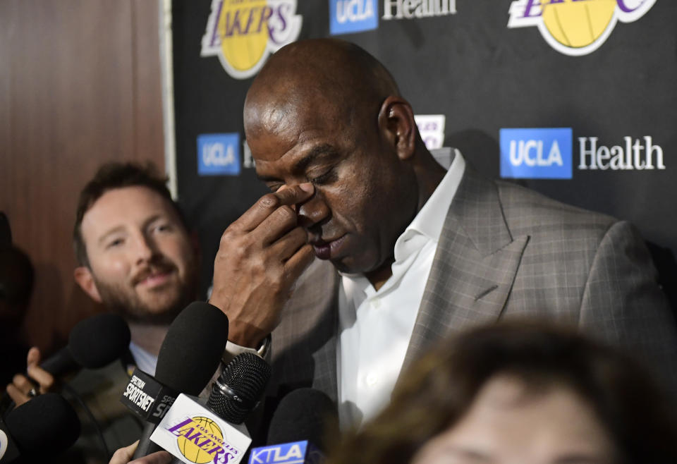 Magic Johnson holds the arch of his nose.