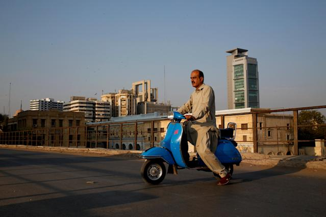 "<p>Journalist Arif Balouch, 48, poses for a photograph with his 1980 model Vespa scooter in Karachi, Pakistan, March 2, 2018. ""For me, a Vespa scooter is like a family tradition. My father used to ride this and I myself find this very good as it has two separate comfortable seats which is uncommon, it has a compartment to keep things which is also uncommon and for safety it guards your knees during accidents. I would say it's the BMW of scooters,"" Balouch said. (Photo: Akhtar Soomro/Reuters) </p>"