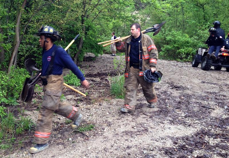 In this May 22, 2013, file photo rescue personnel work near the scene of a rockslide in St. Paul, Minn. Authorities said Thursday, May 23, 2013, they've recovered the body of a child missing since a rockslide killed a classmate and left two others injured at the park along the Mississippi River. (AP Photo/The Star Tribune, Nicole Norfleet)  MANDATORY CREDIT; ST. PAUL PIONEER PRESS OUT; MAGS OUT; TWIN CITIES TV OUT