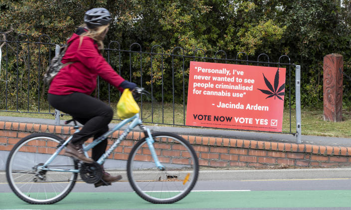 Image: A cyclist rides past a sign in support of making marijuana legal in Christchurch, New Zealand (Mark Baker / AP)