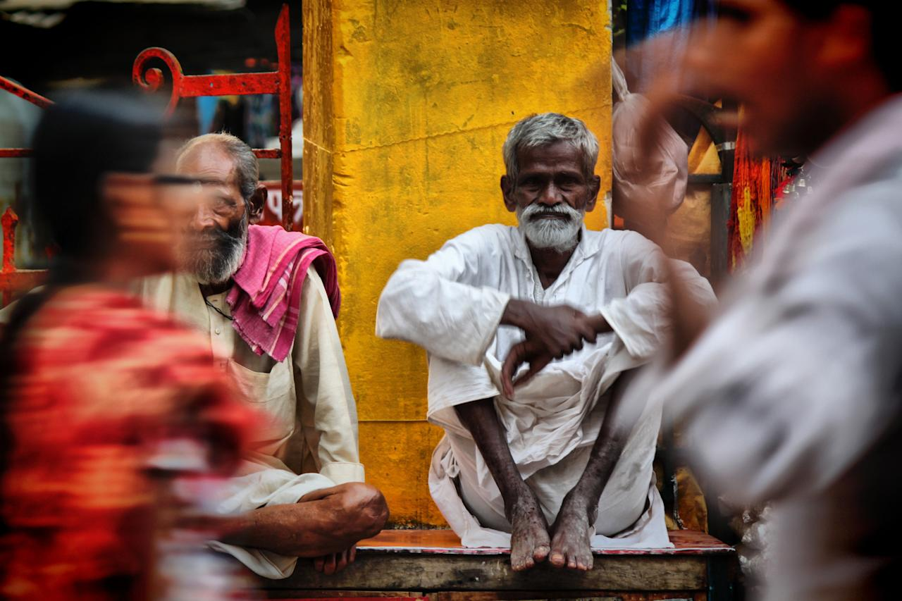 A man looks straight at the camera as pedestrians pass him by. The image was taken by Monika Mukherjee and is one of the entries into the competition (Monika Mukherjee)