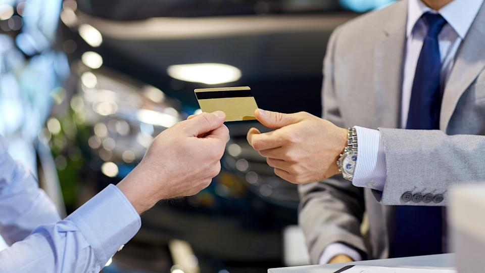 auto business, sale and people concept - close up of customer giving credit card to car dealer in auto show or salon.