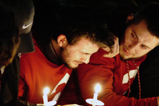 Luke Falk (left) cries during a candlelight memorial service for Tyler Hilinski. (AP)
