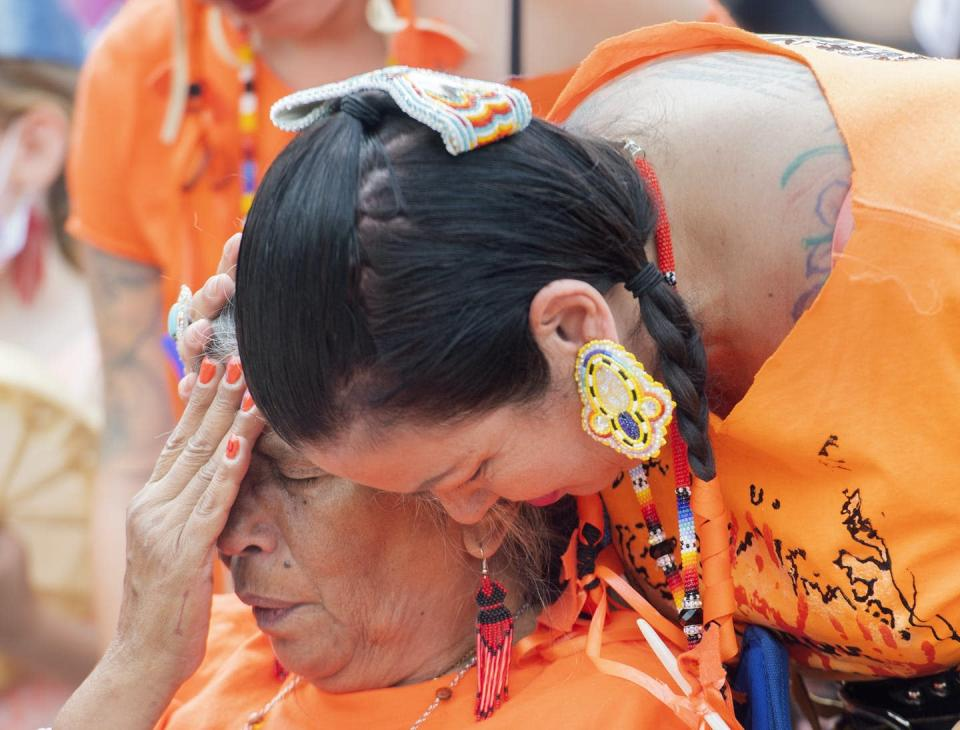 A woman weeps while another consoles her, both wearing orange T-shirts.