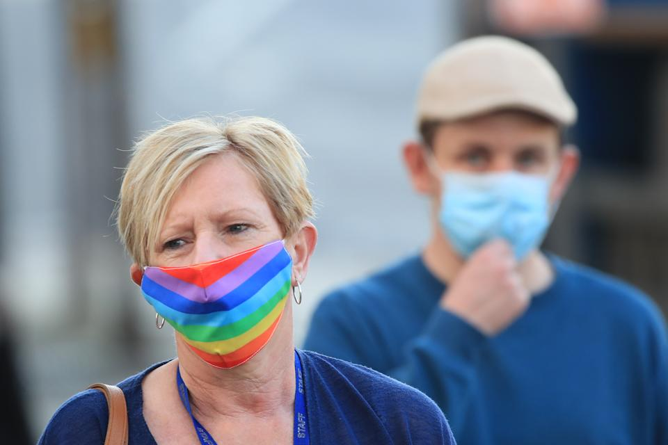 A woman wearing a face mask walks through the centre of Bradford, West Yorkshire, one of the areas where new measures have been implemented to prevent the spread of coronavirus. Stricter rules have been introduced for people in Greater Manchester, parts of East Lancashire, and West Yorkshire, banning members of different households from meeting each other indoors. (Photo by Danny Lawson/PA Images via Getty Images)
