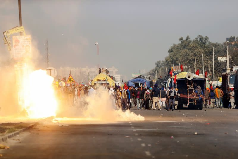 Flames emerge from tear gas released by the police to stop farmers opposing the newly passed farm bills from entering the national capital Delhi, at Singhu border, India