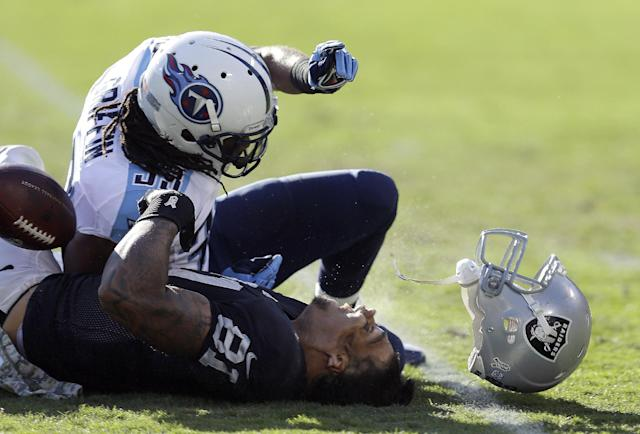 FILE - In this Nov. 14, 2013, file photo, Oakland Raiders tight end Mychal Rivera (81) loses his helmet after being hit by Tennessee Titans free safety Michael Griffin during the second quarter of an NFL football game in Oakland, Calif. Griffin was penalized on the play and served a one-game suspension for the hit. (AP Photo/Ben Margot, File)