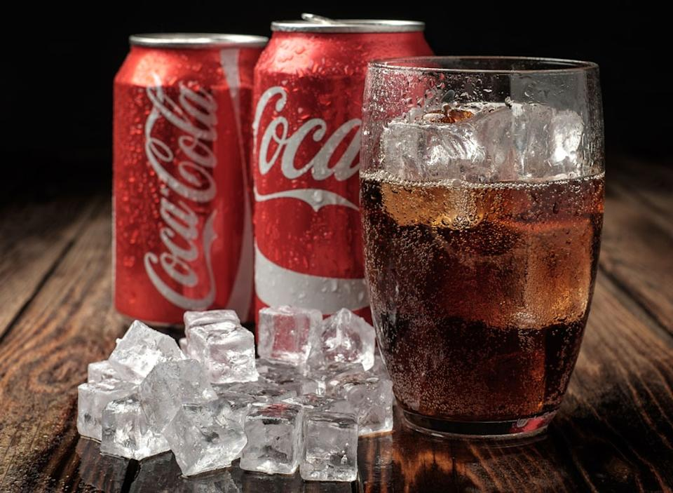 can of coke soda next to glass