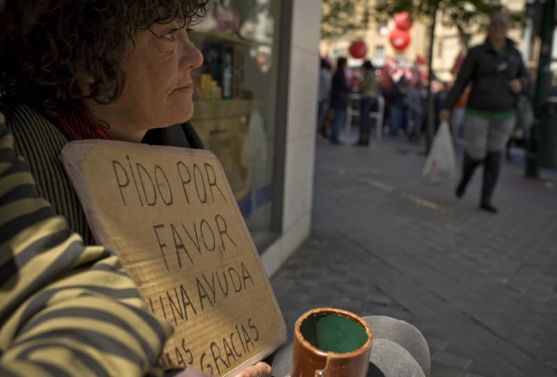 Alice, a homeless woman, left,  begs for alms, as people protest against the government's tough new labor reforms and cutbacks in Pamplona, northern Spain, Tuesday, May 1, 2012. Banging drums and waving flags, tens of thousands of workers marked May Day in European cities Tuesday with a mix of anger and gloom over austerity measures imposed by leaders trying to contain the eurozone's intractable debt crisis. (AP Photo/Alvaro Barrientos)