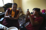 Jalue Dorje, left, and his cousin Delek Topgyal, 13, watch videos on their phones after playing the NBA 2K video game between prayer sessions on Monday, July 19, 2021, in Columbia Heights, Minn. (AP Photo/Jessie Wardarski)