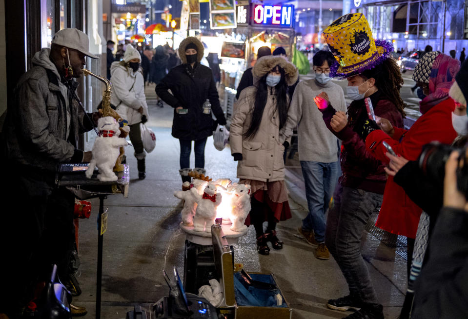 Pedestrians pass by and also watch street entertainment on Eighth Avenue, adjacent to a closed-off Times Square in New York, late Thursday, Dec. 31, 2020, as celebrations have been truncated this New Year's Eve due to the ongoing pandemic. (AP Photo/Craig Ruttle)