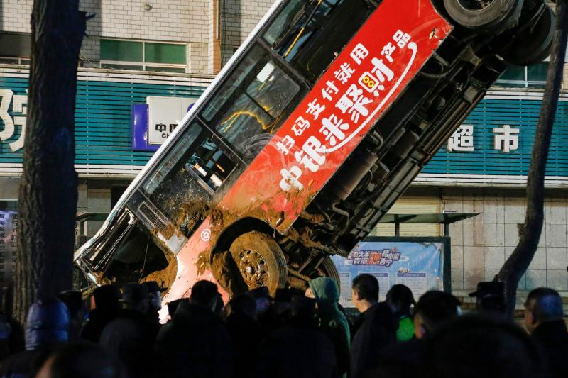 This photo taken on January 13, 2020 shows Chinese rescuers watching as a car is lifted out after a road collapse in Xining in China's northwestern Qinghai province. - An enormous sinkhole swallowed passers-by and a public bus in northwest China, reported state media on January 14, injuring fifteen people while another ten are still missing. (Photo by STR / AFP) / China OUT (Photo by STR/AFP via Getty Images)